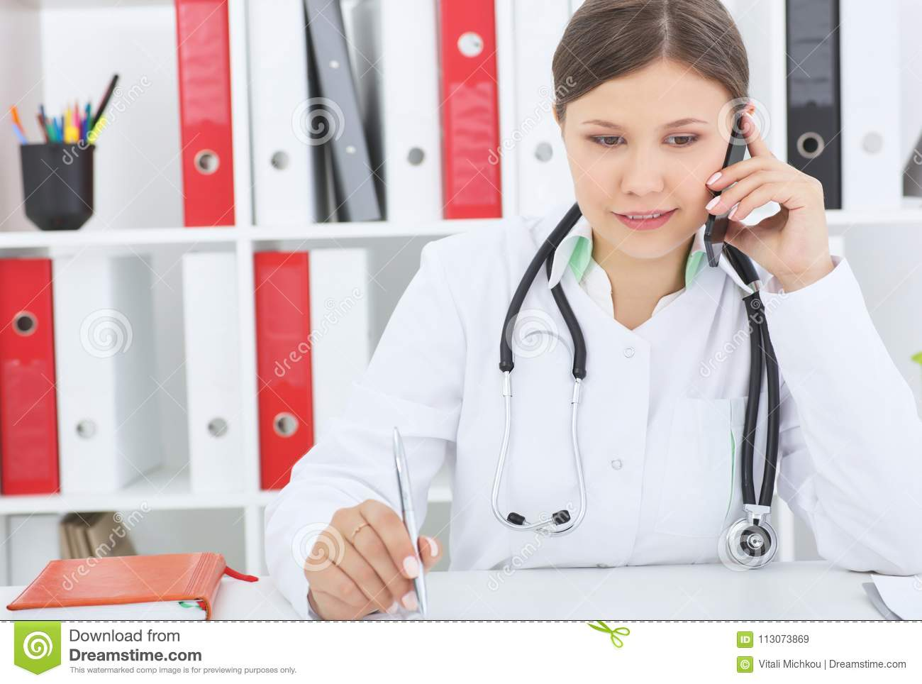 Young female doctor talking on phone at her desk in office.