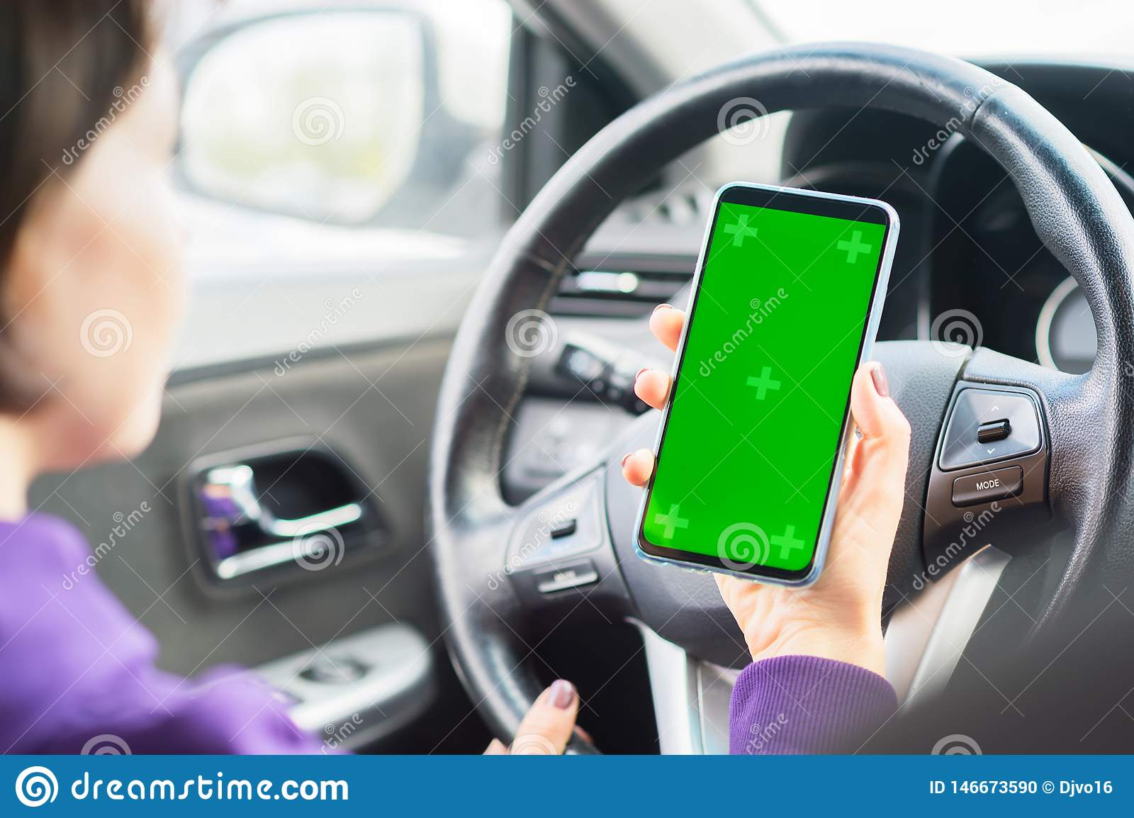 Young female driver using touch screen smartphone in a car. green chroma key on the phone display