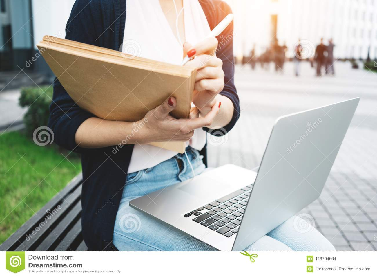 Young female freelancer making labor market research on modern laptop, sits on outdoors in urban street