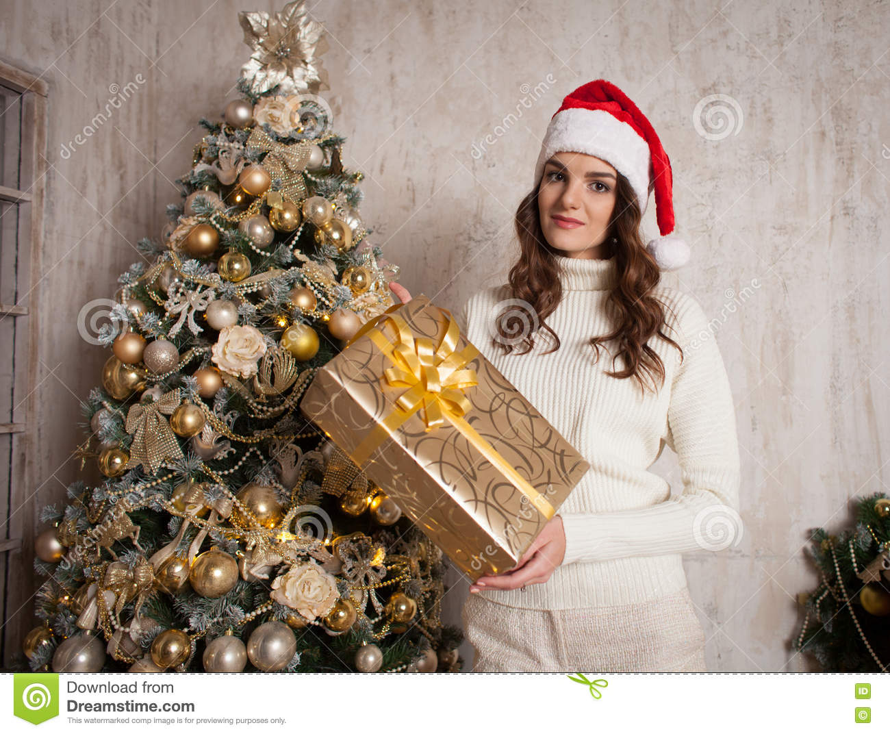Young female with gift box near Christmas tree in cosiness home