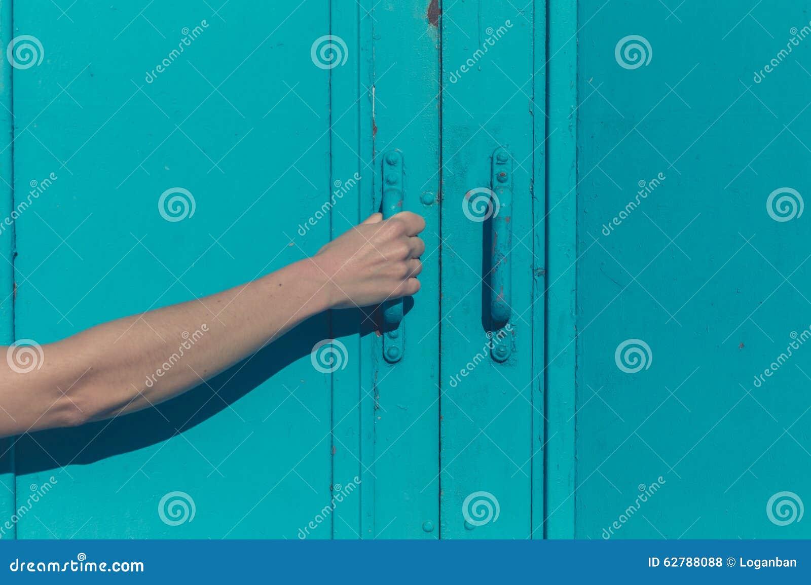 Young female hand grabbing blue door