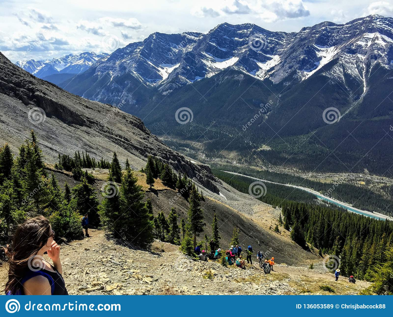 A young female hiker enjoying the view of the Rocky Mountains while hiking to the top of Ha Ling peak