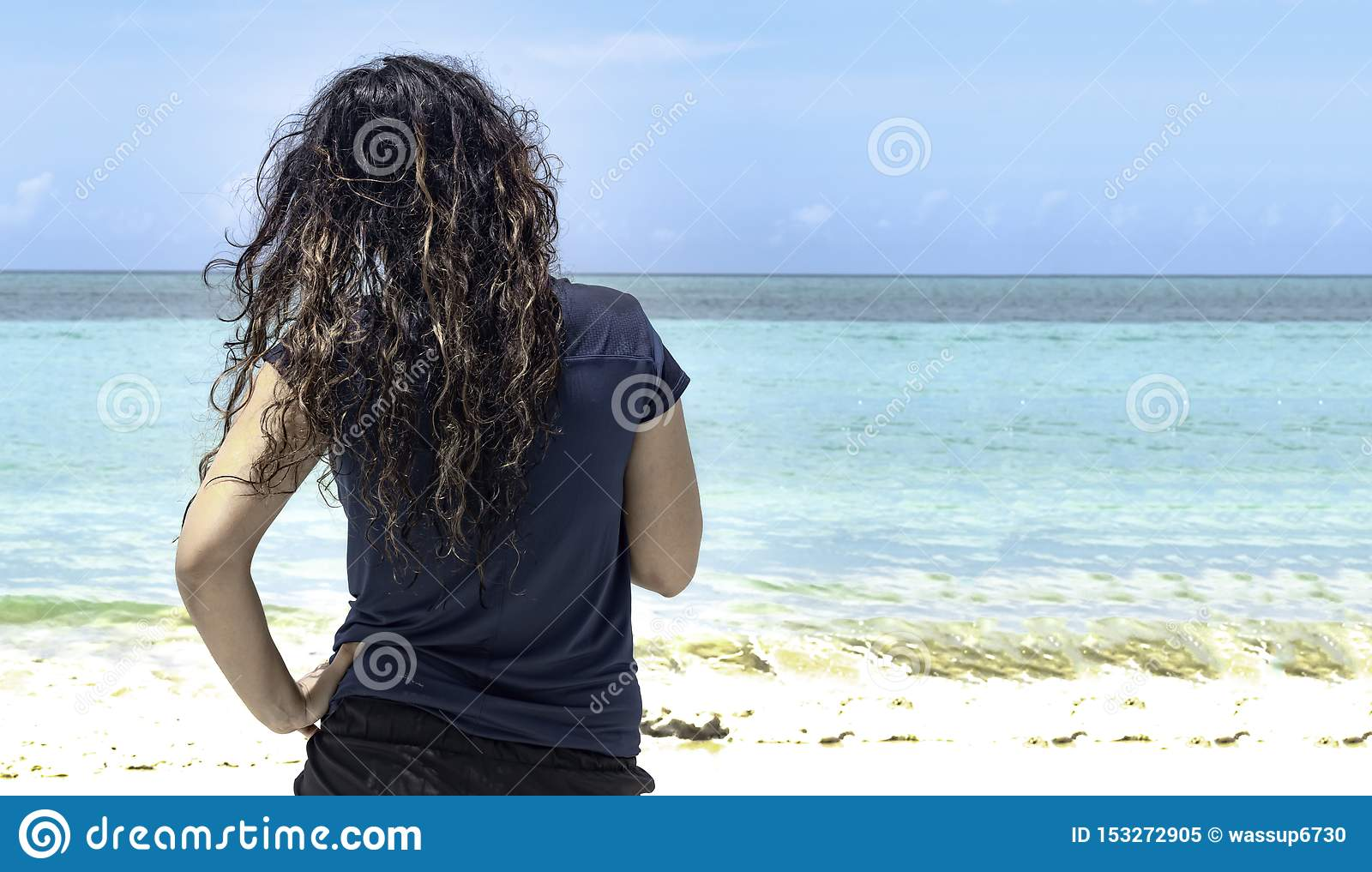 Young Female Lifeguard, with beautiful curly hairs observing swimmers safety, the calm sea of turquoise water, with hands on hips