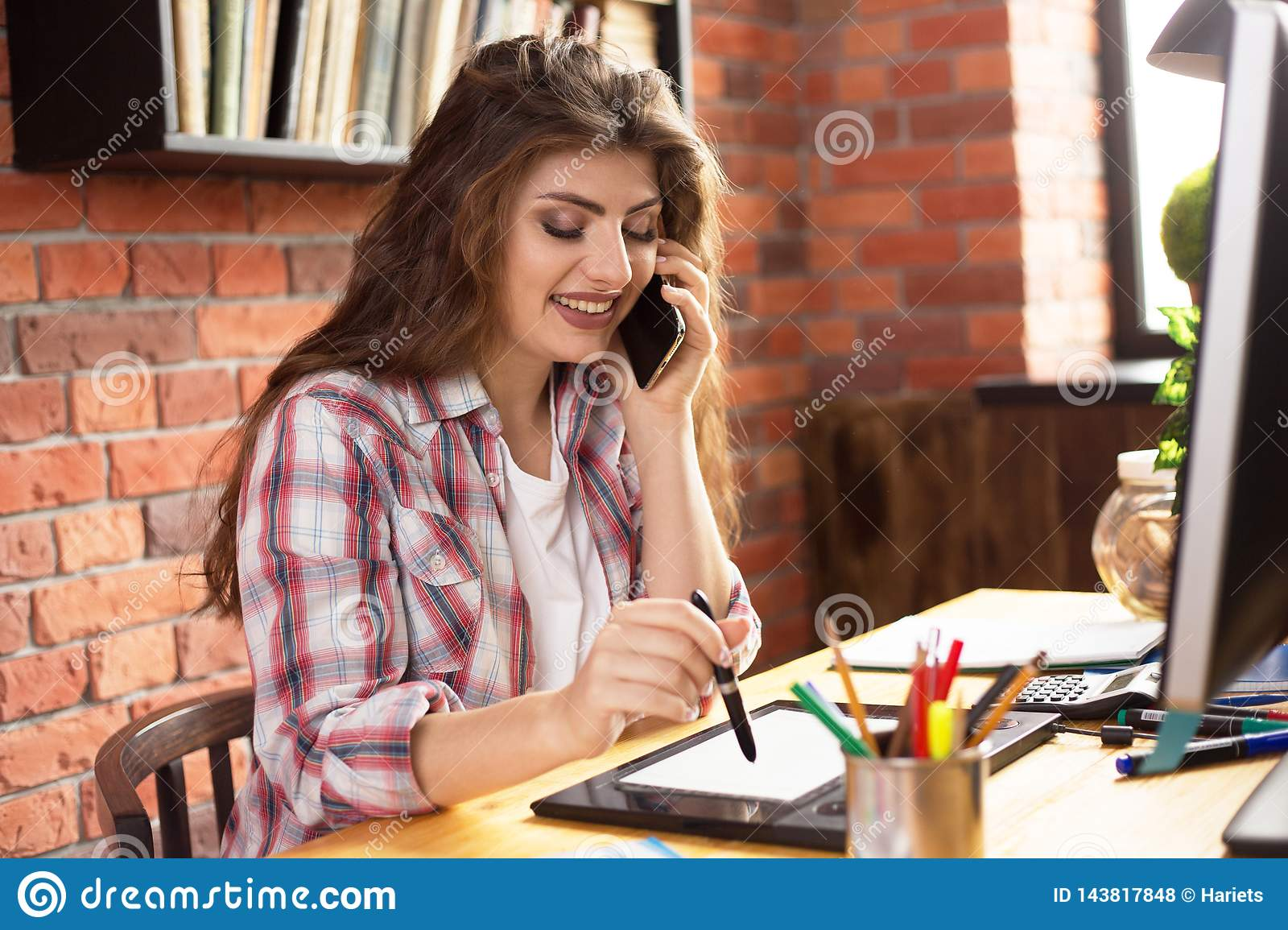 Young female with long hair working with graphic tablet at home or in a loft style office. She talking on a phone and