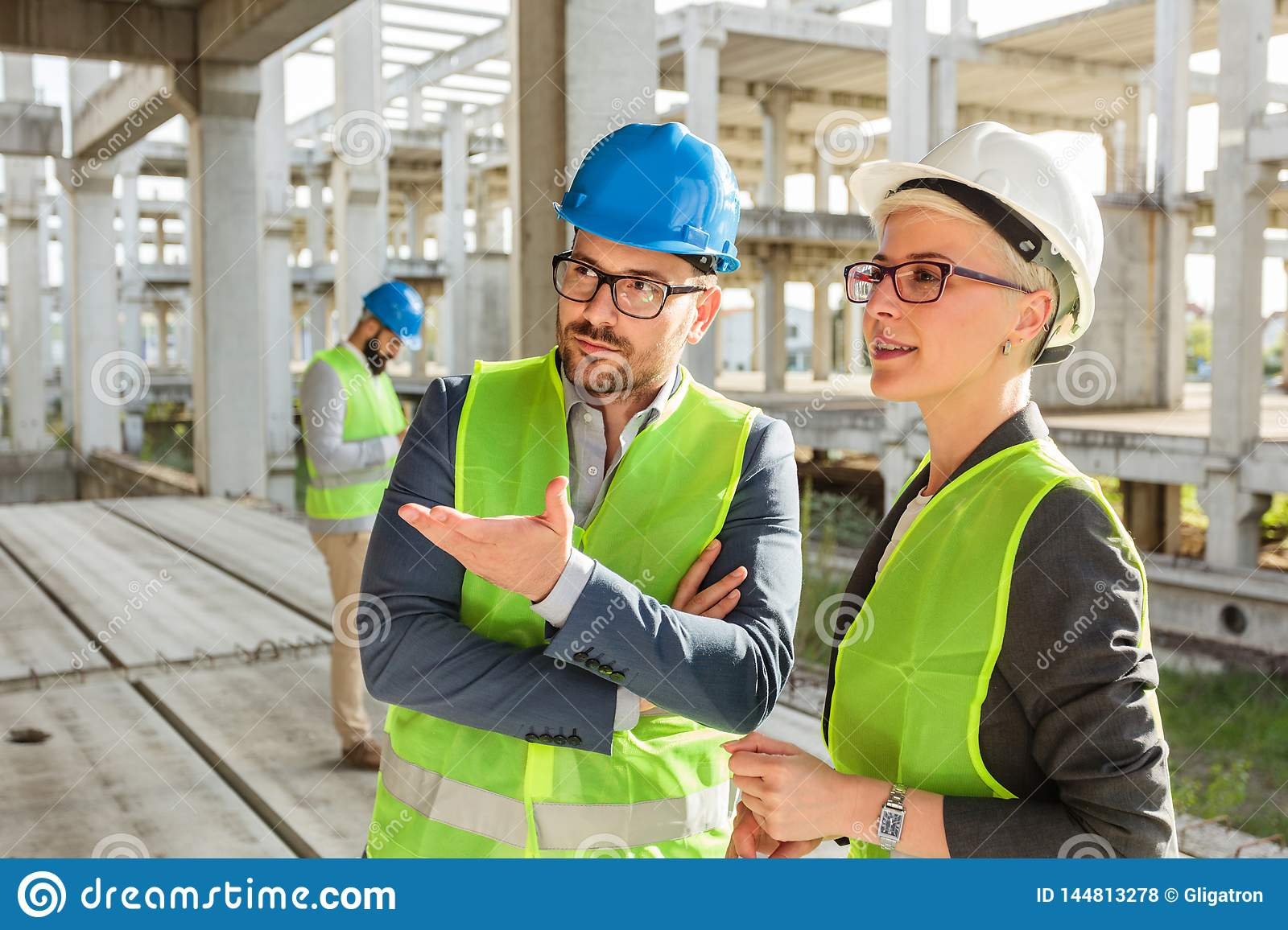 Young male and female architects or business partners talking and discussing  on a construction site