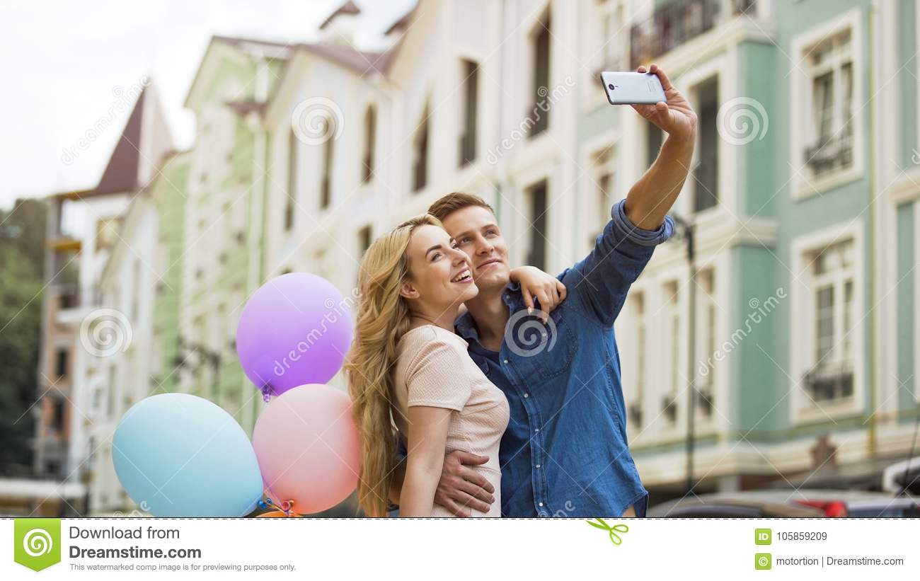 Young female and male in love hugging and taking selfie, romantic memories