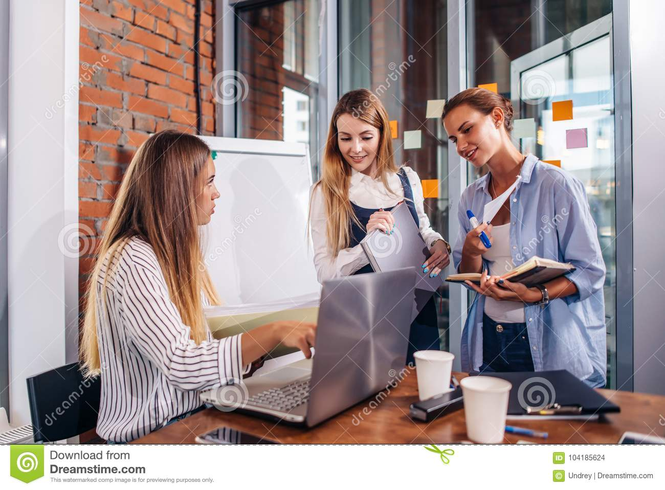 Young female manager sitting at desk pointing at laptop explaining giving tasks to her employees standing writing the