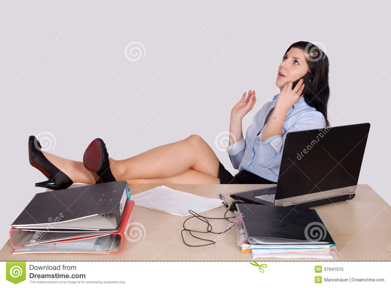 Young Female Office Worker With Feet On Desk Royalty Free