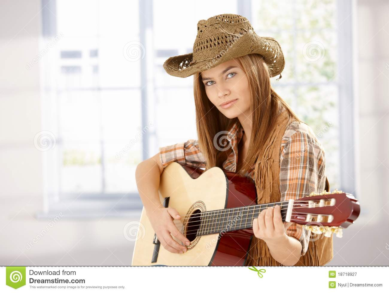 Young female playing guitar in western style stock image for Schaukelstuhl western style