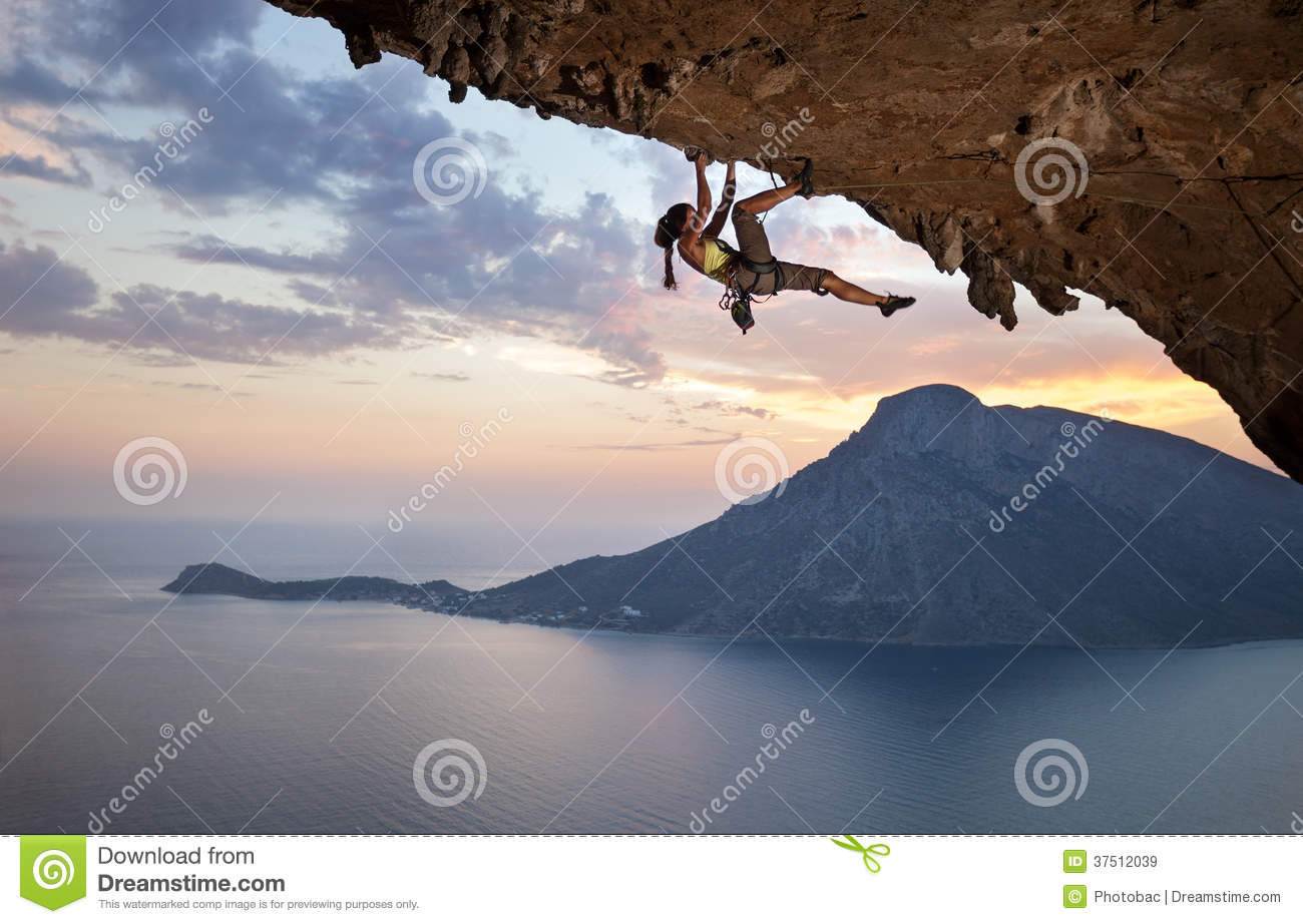 Young female rock climber at sunset