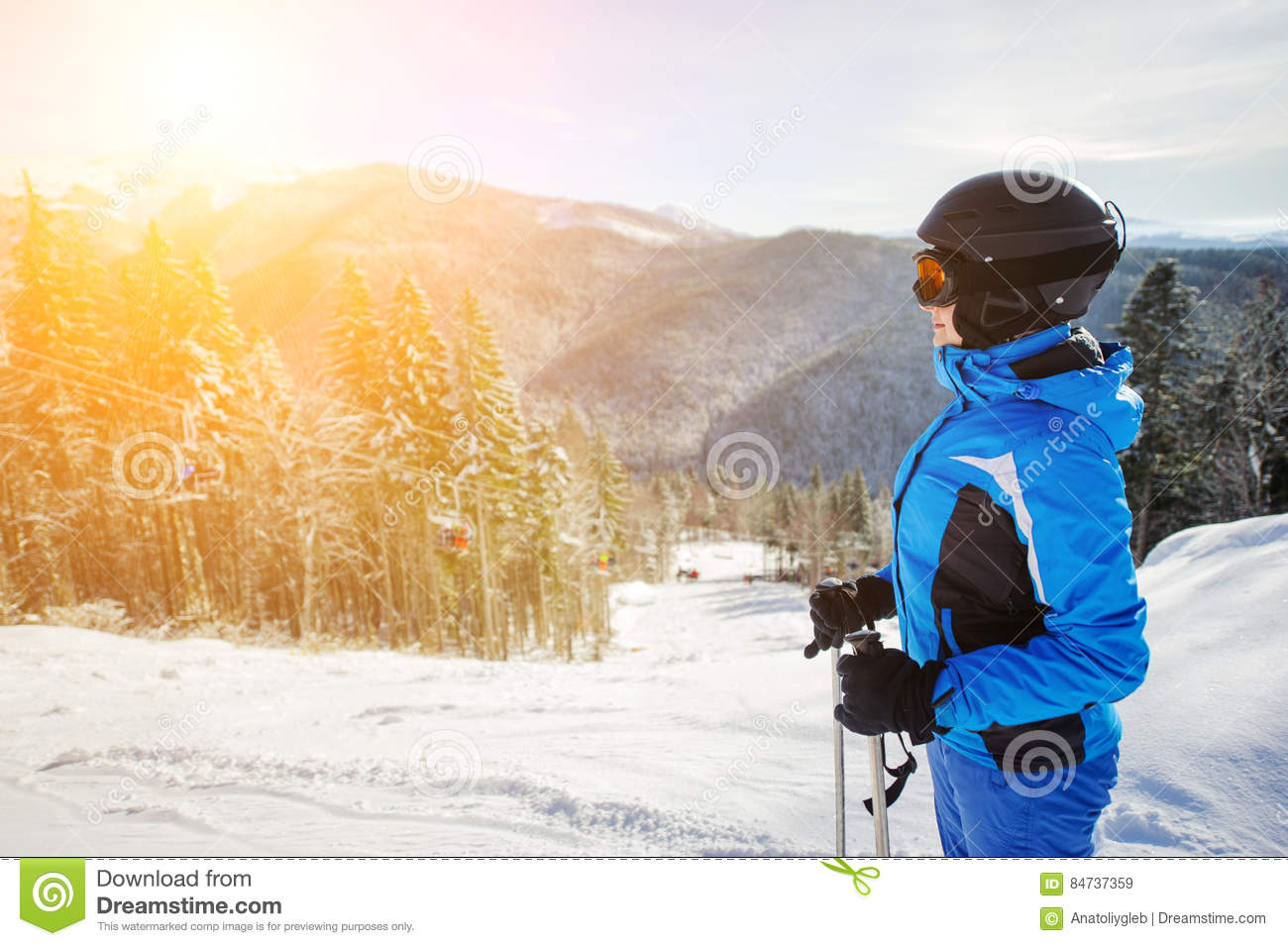 Young female skier against ski lift and winter mountains background