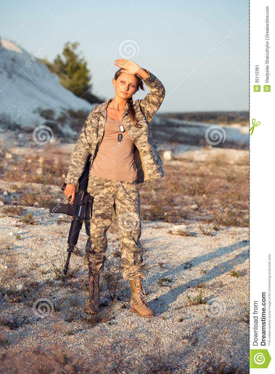 young female soldier dressed in a camouflage with a gun in