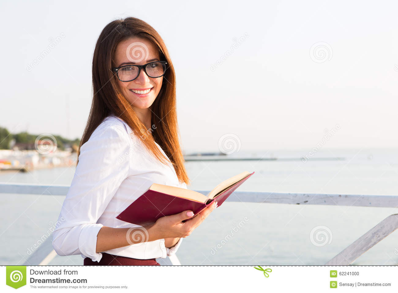 Young female student in reading glasses with the book