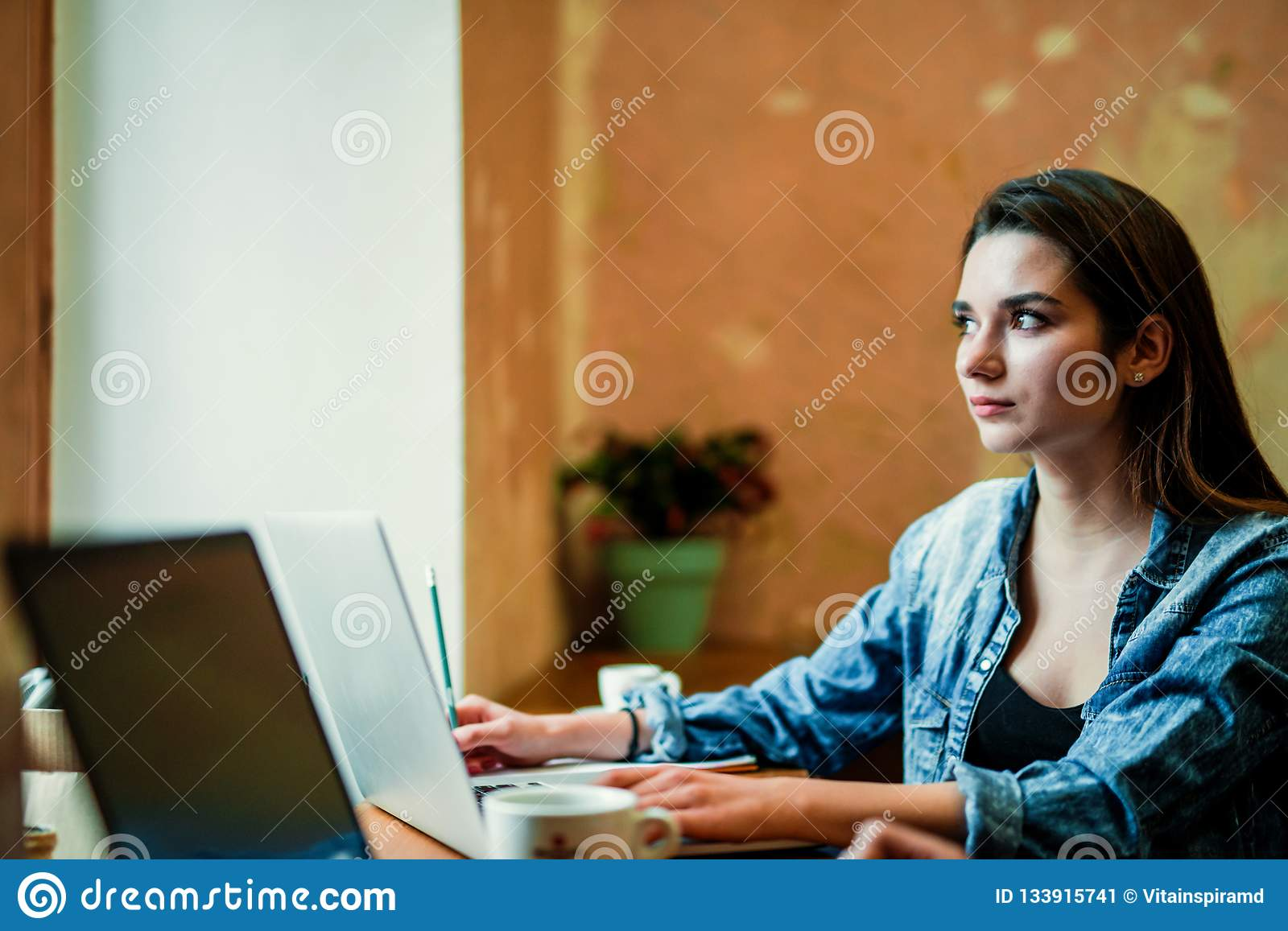 Young female student sits near the window with laptop and look through the window.