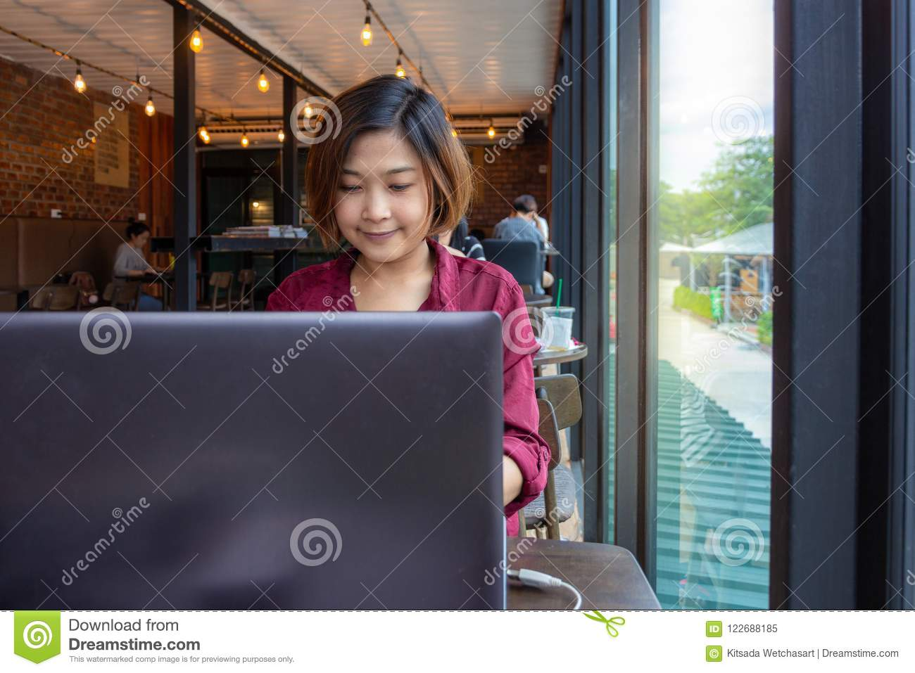 Young female student sitting at table and typing on laptop