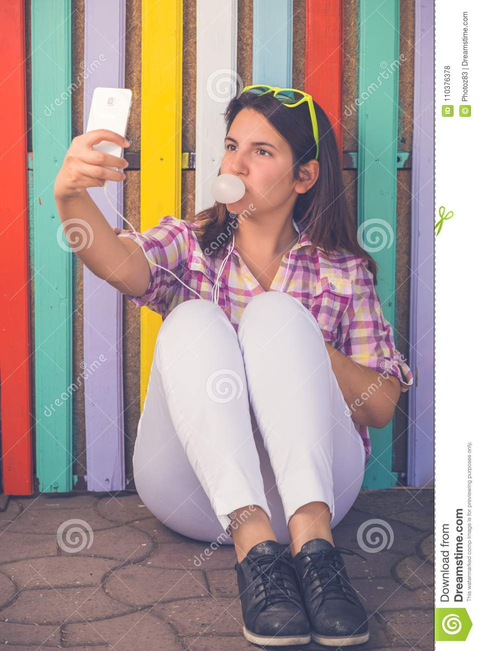 Young female taking selfie in front of colorful wooden wall