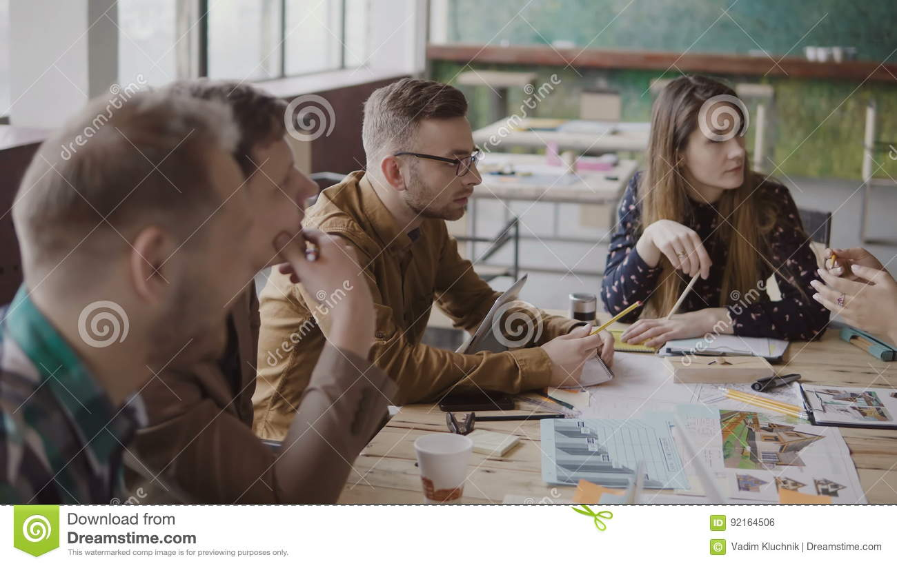 Young female team leader talking with small multiracial group of people. Business meeting of start-up company in office.