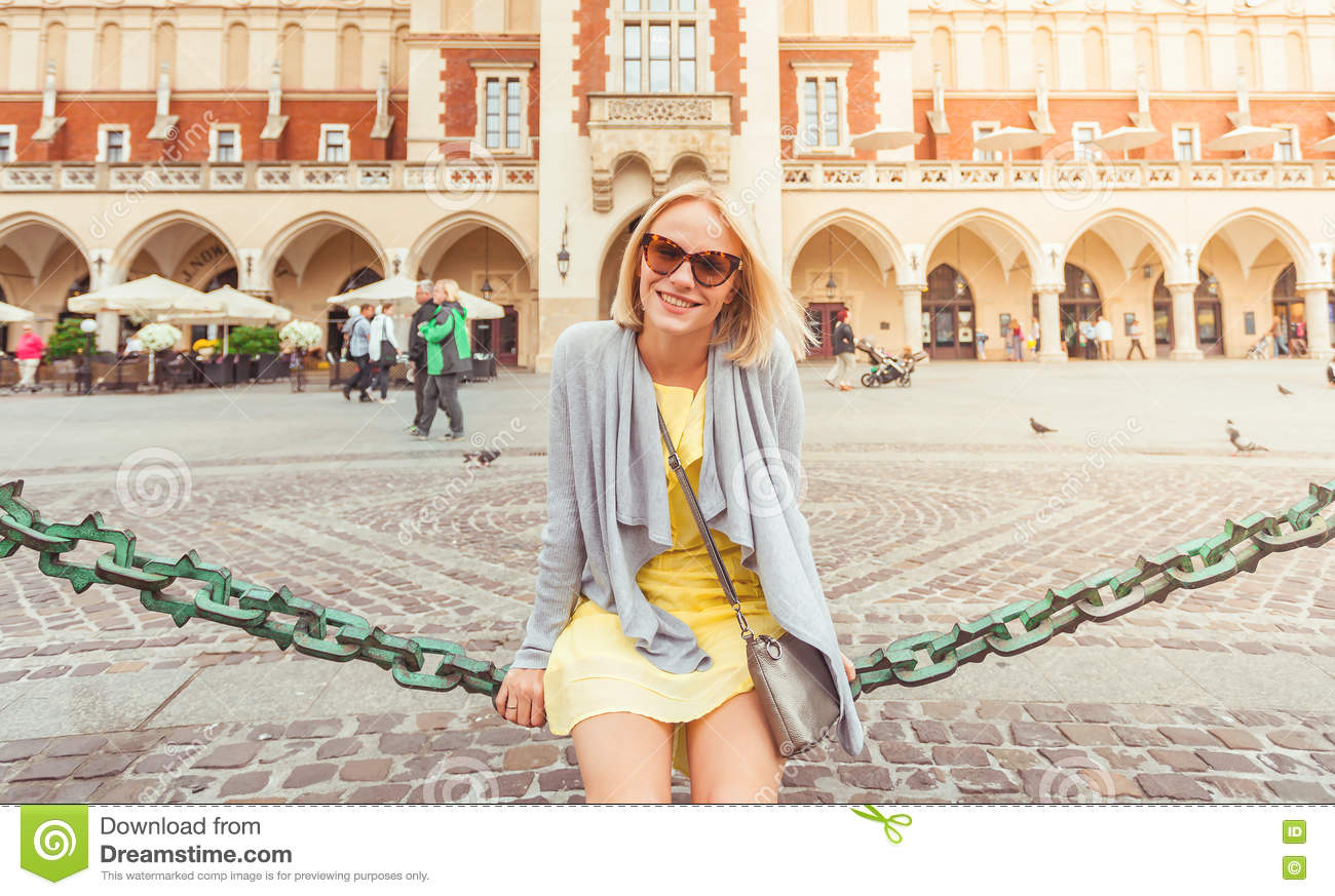 Young female tourist sitting near Cloth Hall in the old city center of Krakow