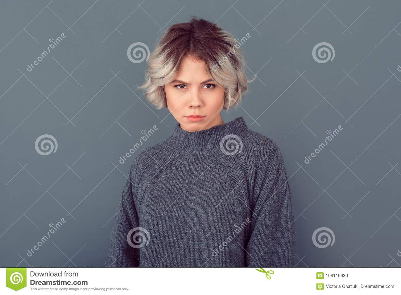 Young woman in a grey sweater studio picture on grey background cautious