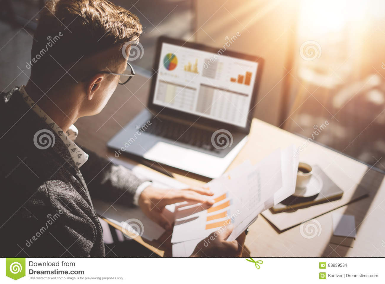 Young finance market analyst in eyeglasses working at sunny office on laptop while sitting at wooden table. Businessman