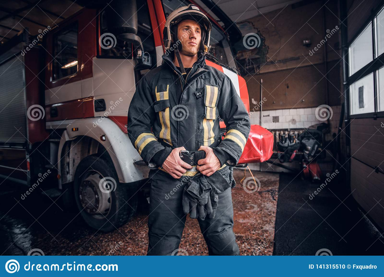 Young fireman wearing protective uniform standing next to a fire engine in a garage of a fire department