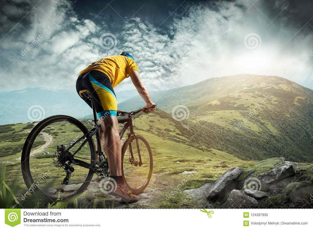 The young fit man in helmet conquering mountains on a bicycle.
