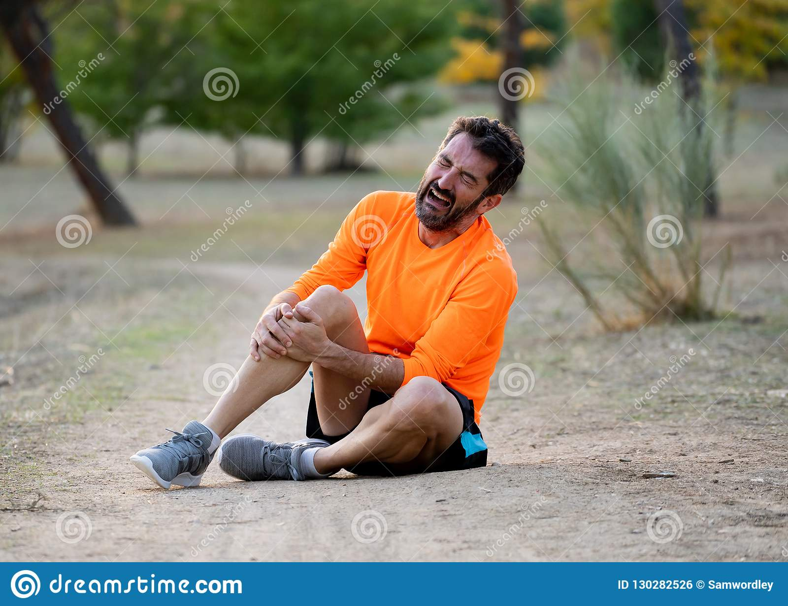 5c351b5269e Young fit man holding knee with his hands in pain after suffering muscle  injury broken bone leg pain sprain or cramp during a running workout in  park ...