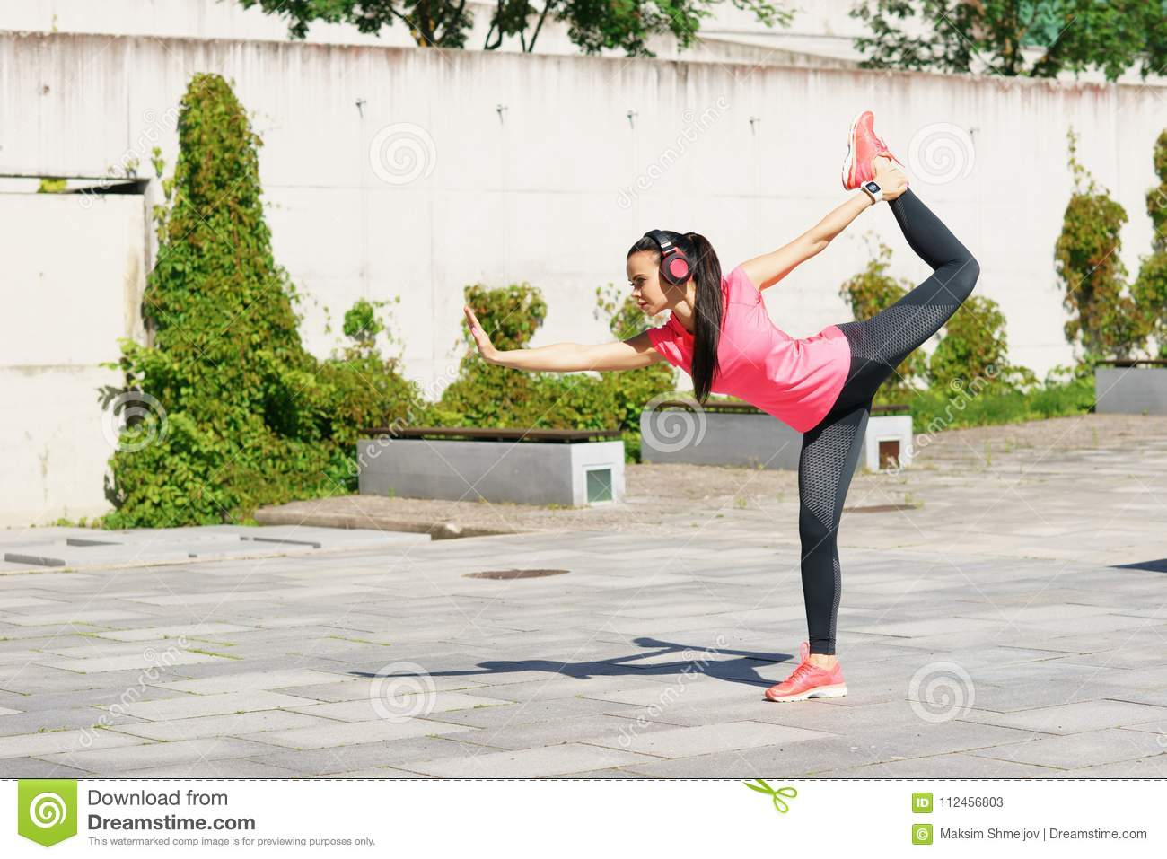 Young, fit and sporty woman doing yoga exercise outdoor. Fitness, sport, urban and healthy lifestyle concept.