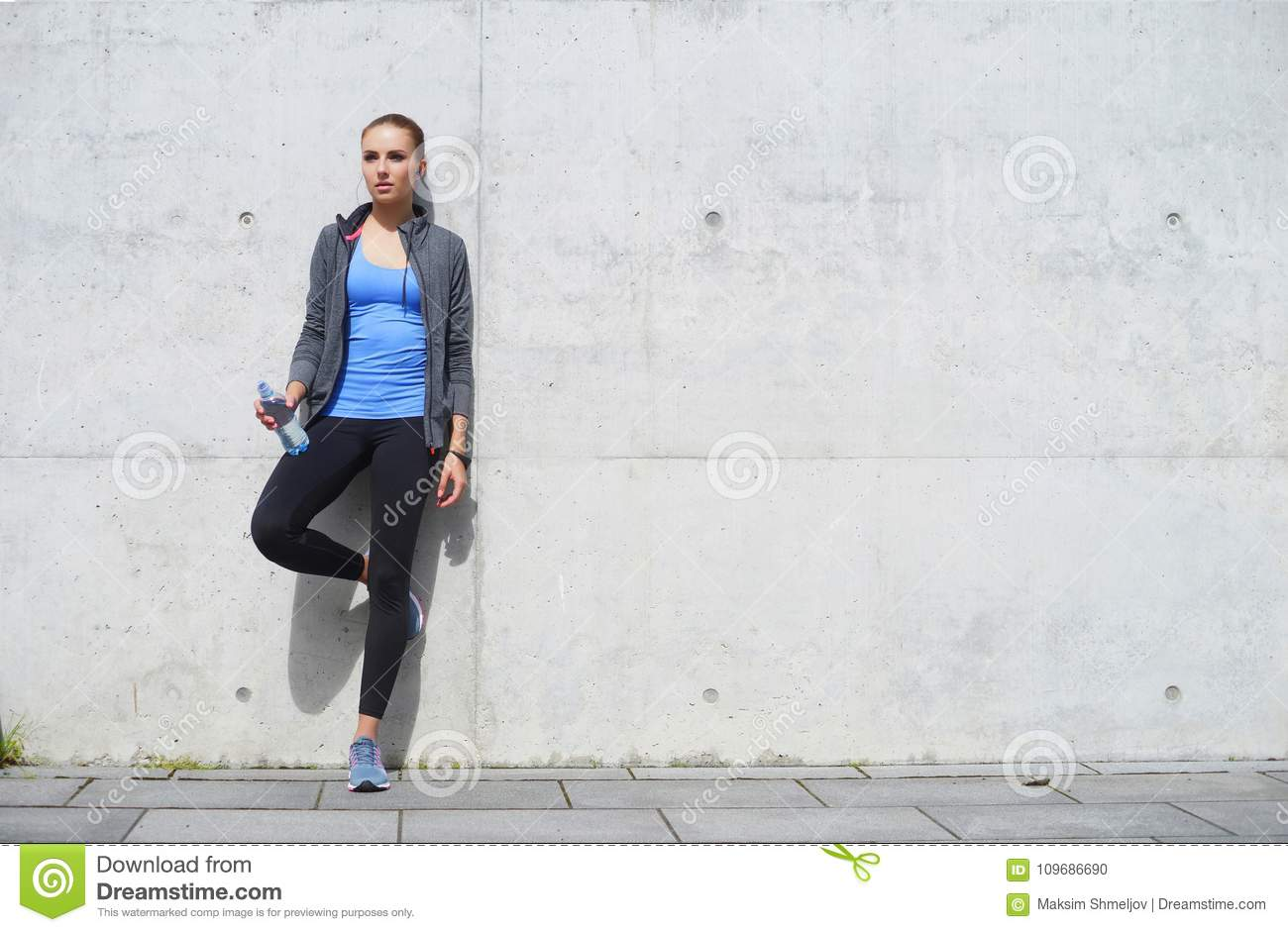Young, fit and sporty woman resting after the training. Fitness, sport, urban jogging and healthy lifestyle concept.
