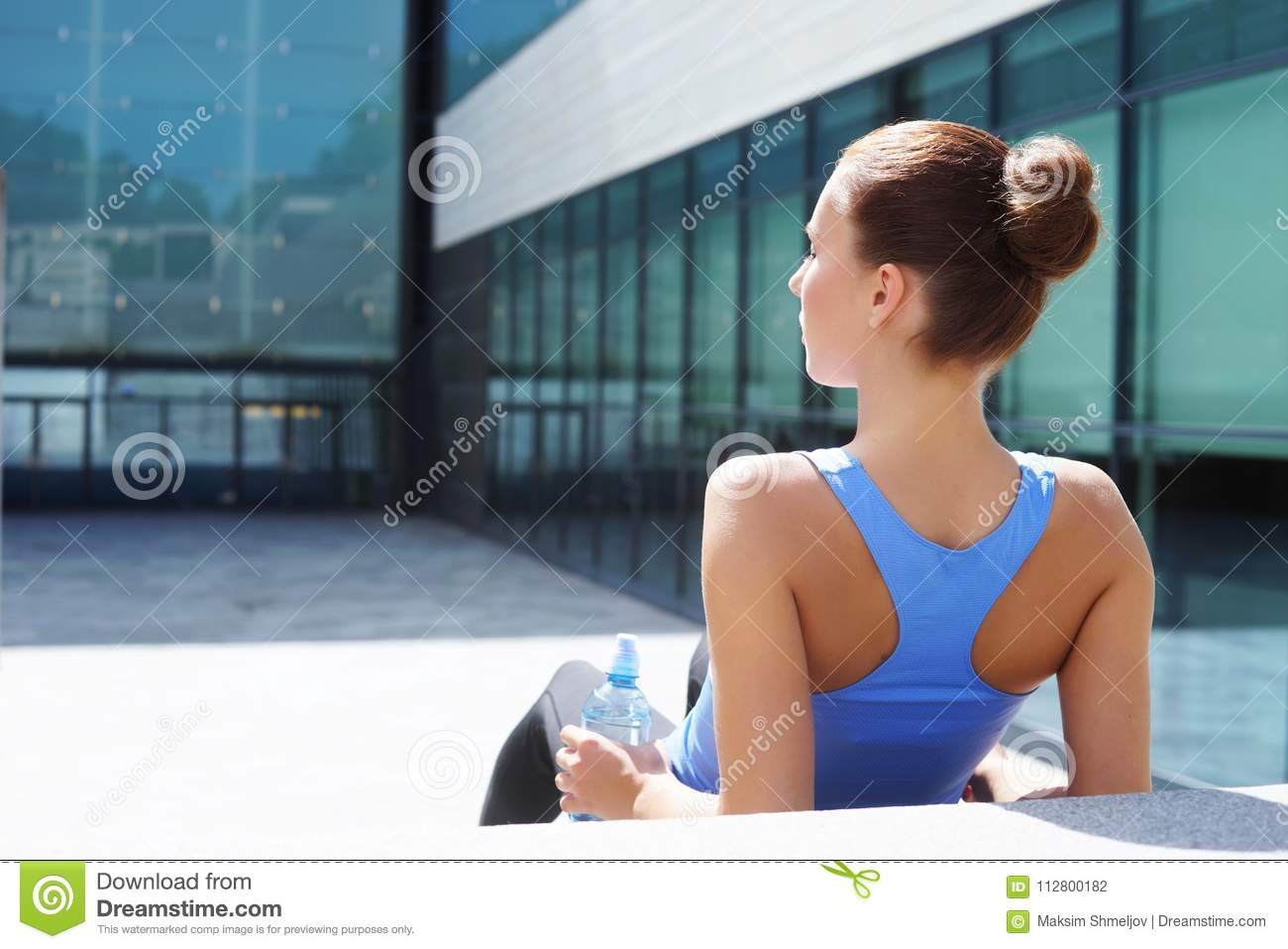 Young, fit and sporty girl preparing for urban jogging. Fitness, sport and healthy lifestyle concept.