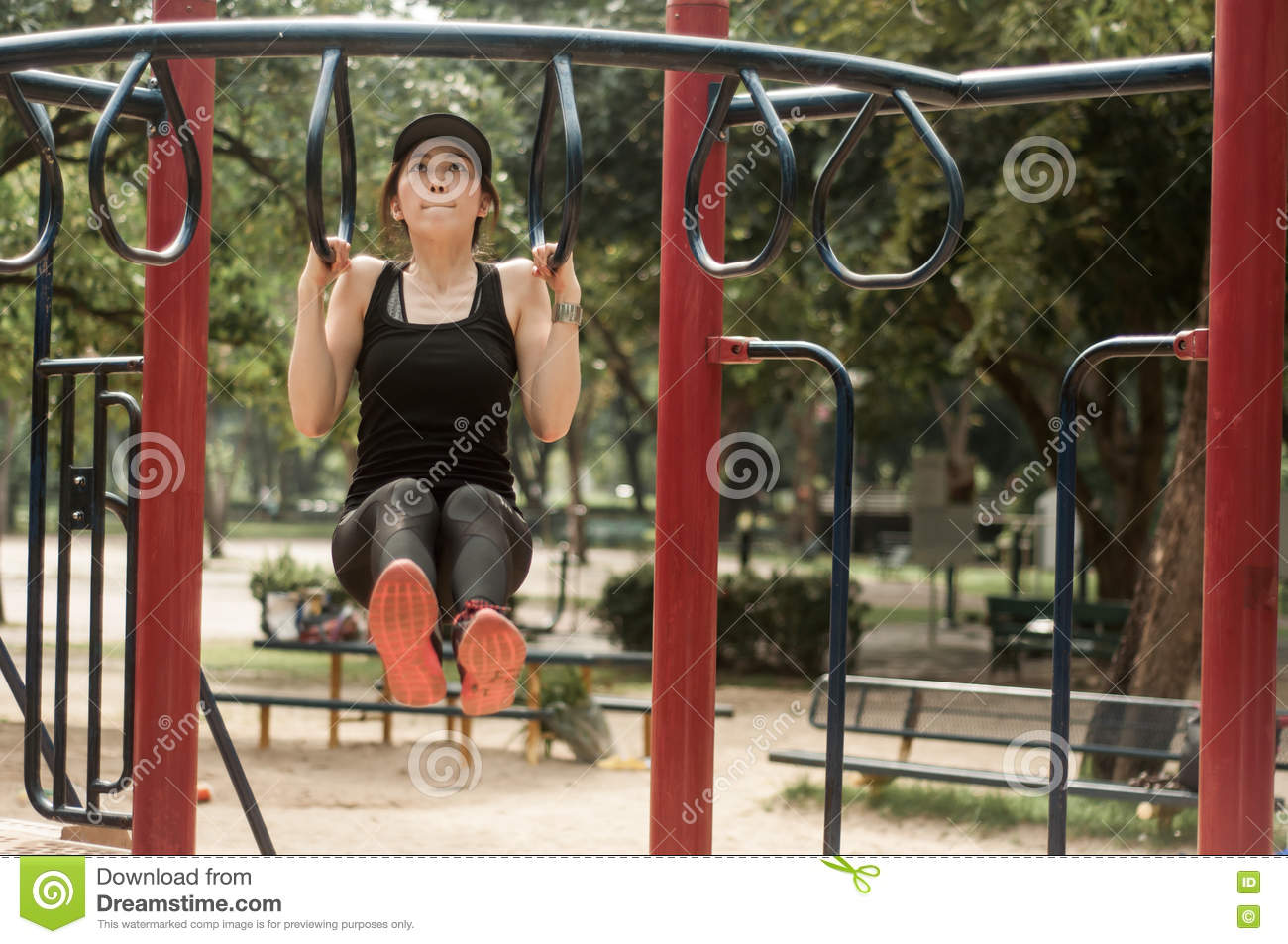 Young fit woman doing a pull up workout at a playground