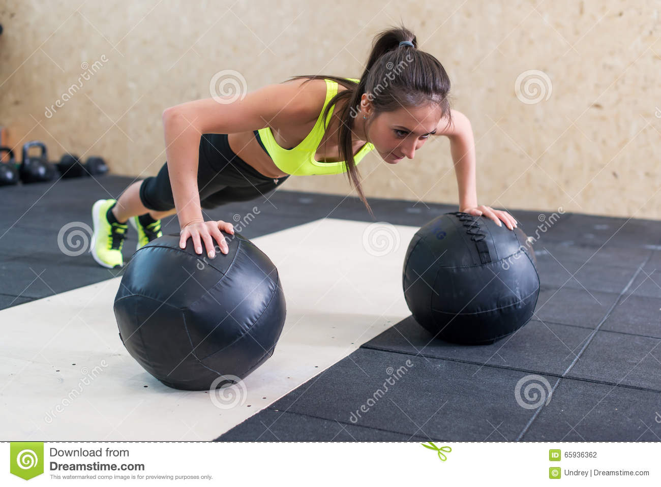 Young fit woman doing push up on medicine ball at gym.