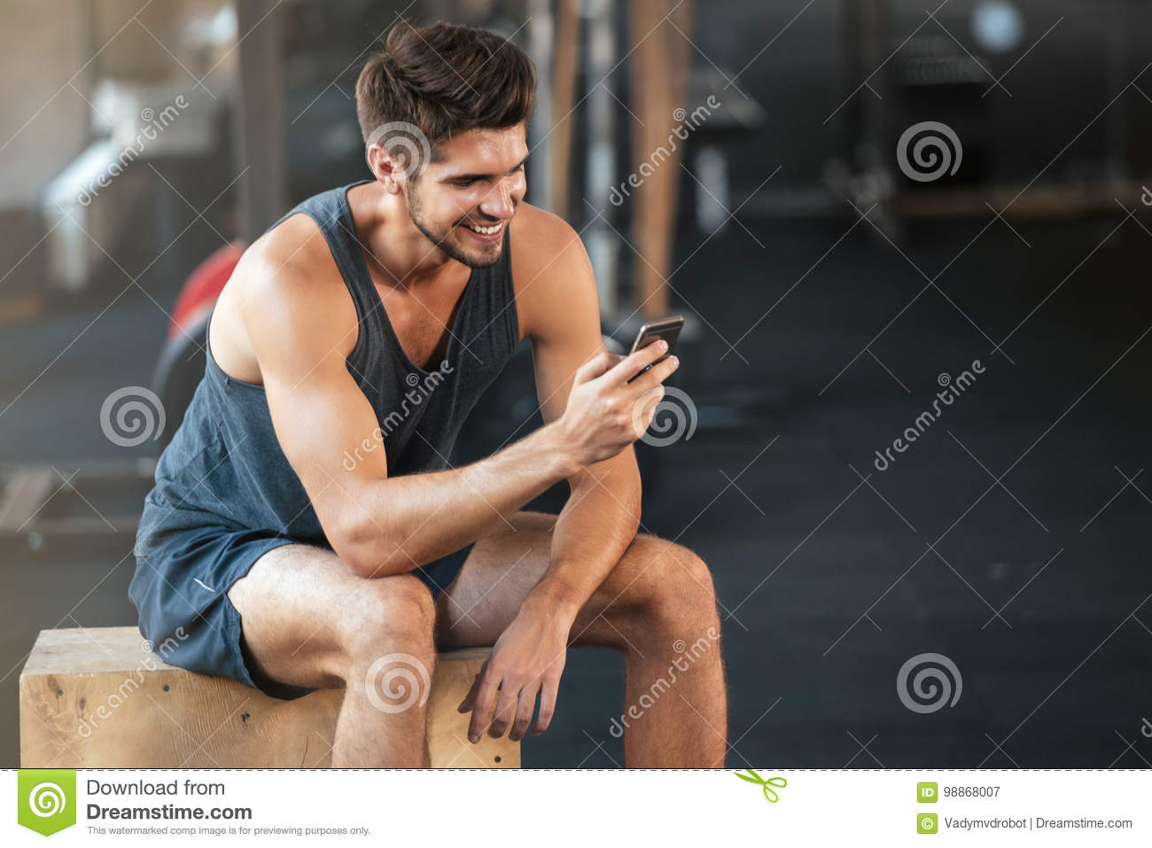 Young fitness man sits on the box