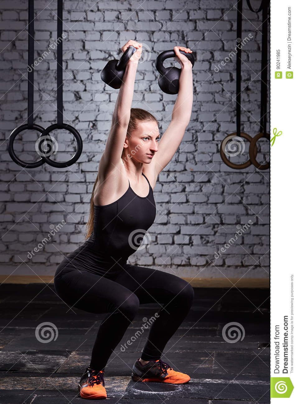 Young fitness woman doing crossfit workout with kettlebell against brick wall.