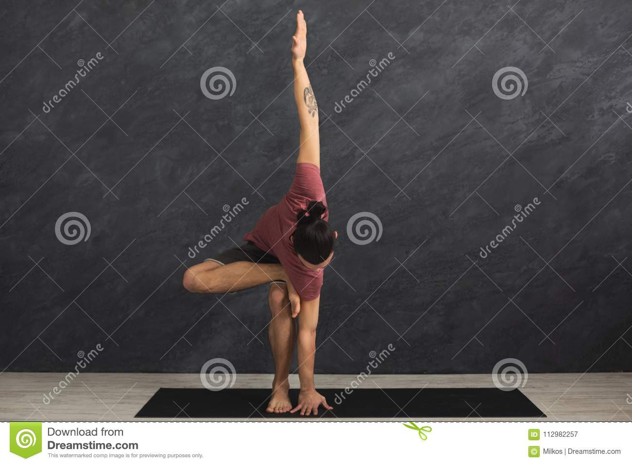 Young flexible man practicing yoga at gym