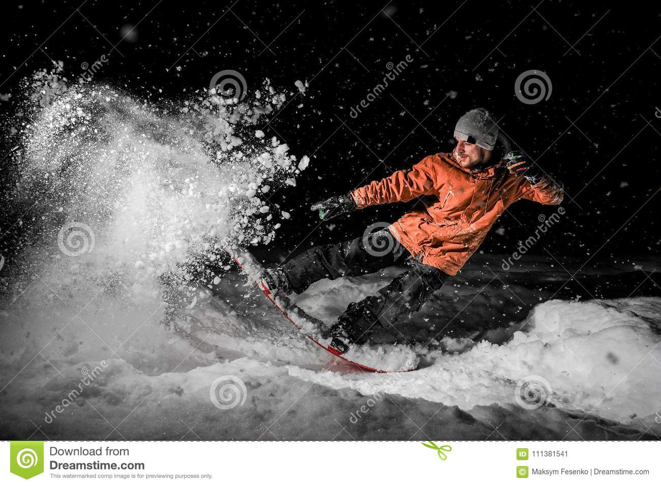 Young freeride snowboarder jumping in snow at night