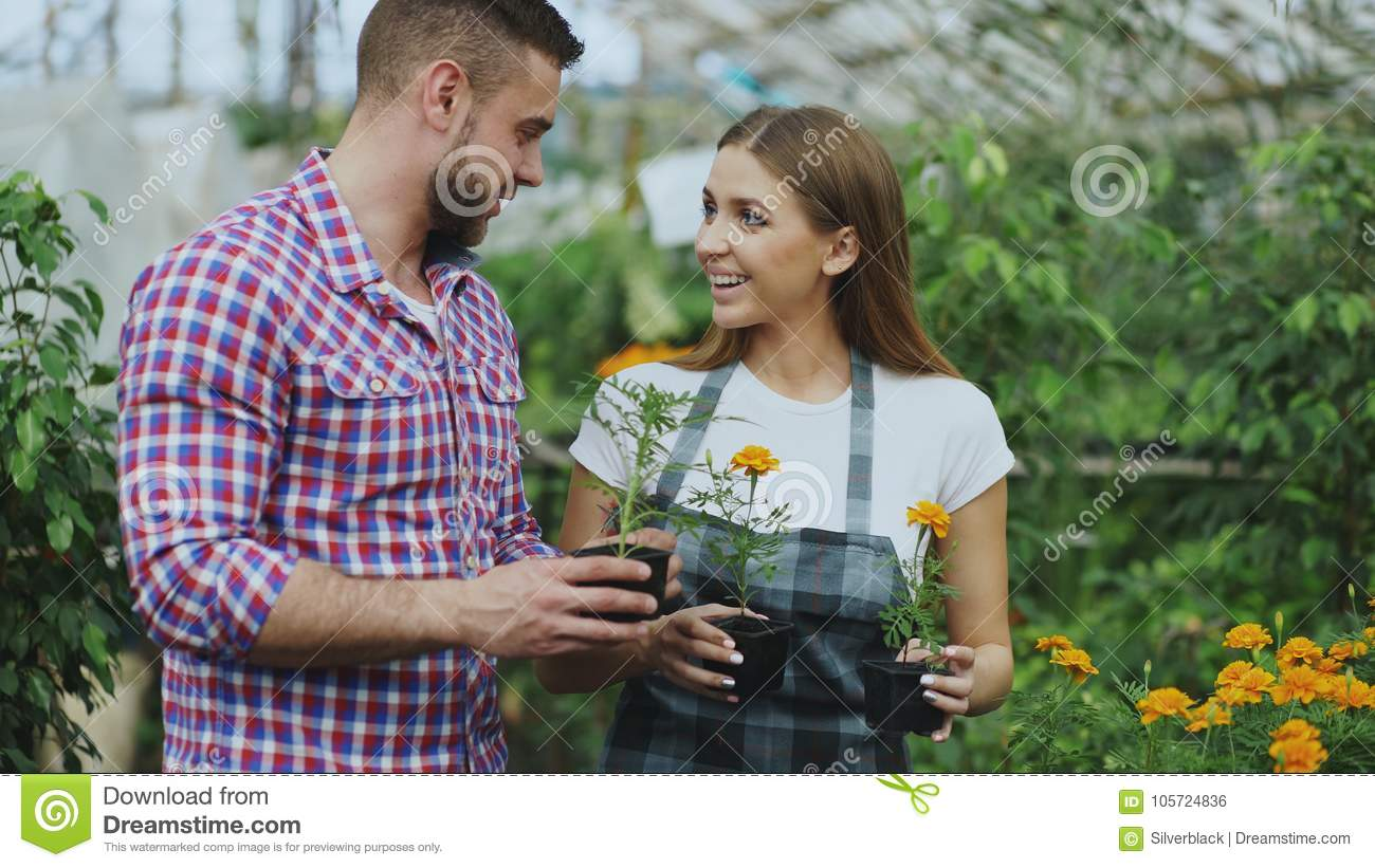 Young friendly woman florist talking to customer and giving him advice while working in garden center