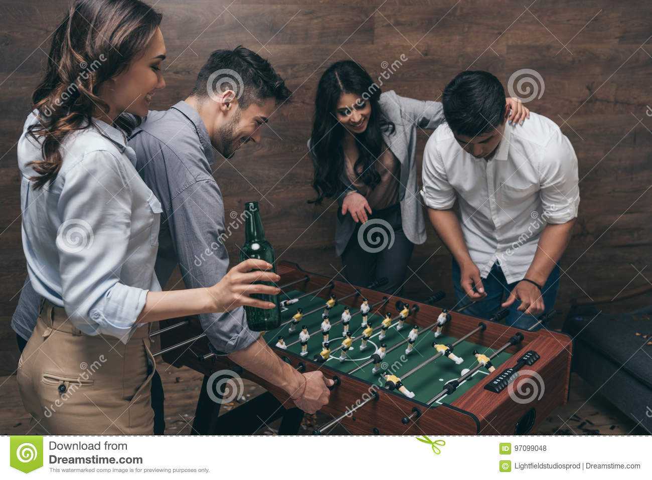 Young friends drinking beer and playing foosball indoors