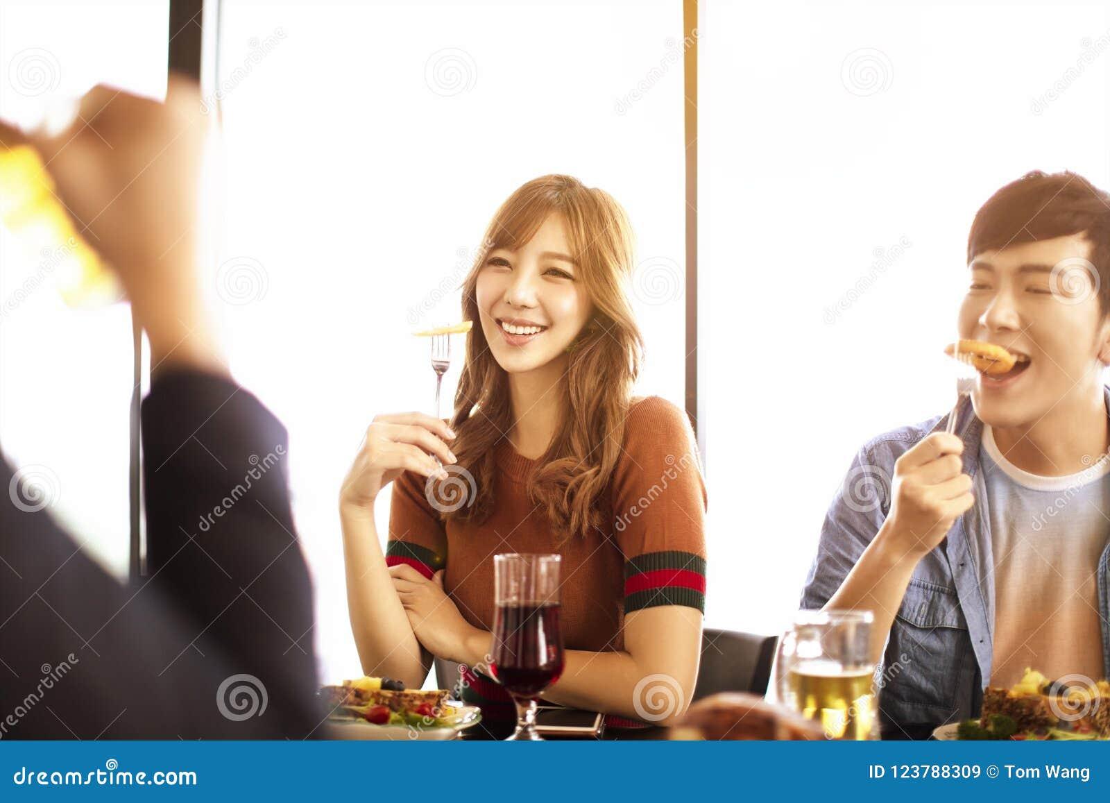 young friends enjoy dinner in restaurant.