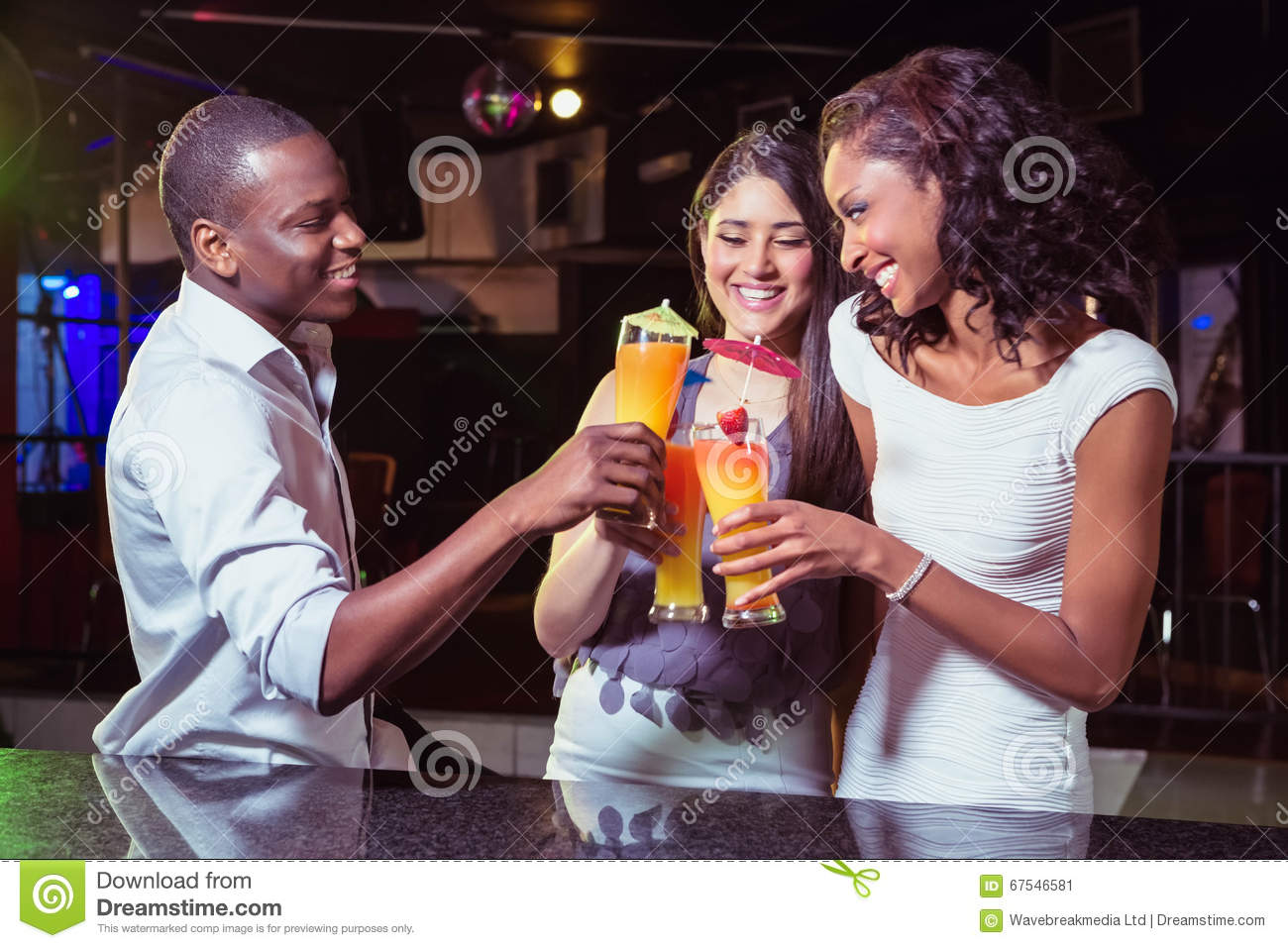 Young friends enjoying while having cocktail drinks at bar counter