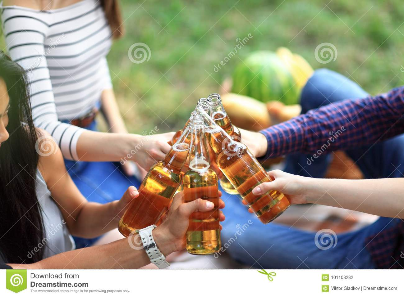 Young Friends Having Fun Outdoors, Clinking Bottles Of ...