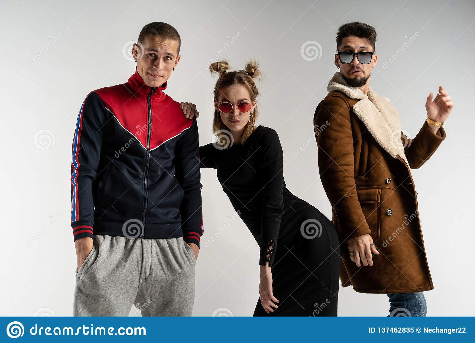 Young friends having fun together, beautiful woman standing between two handsome men