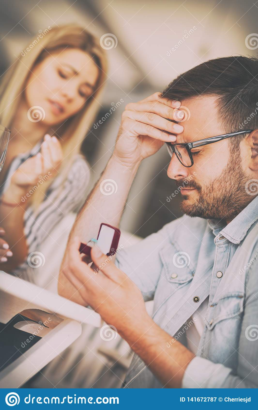 Young frustrated sad man holding wedding engagement ring, proposal rejection