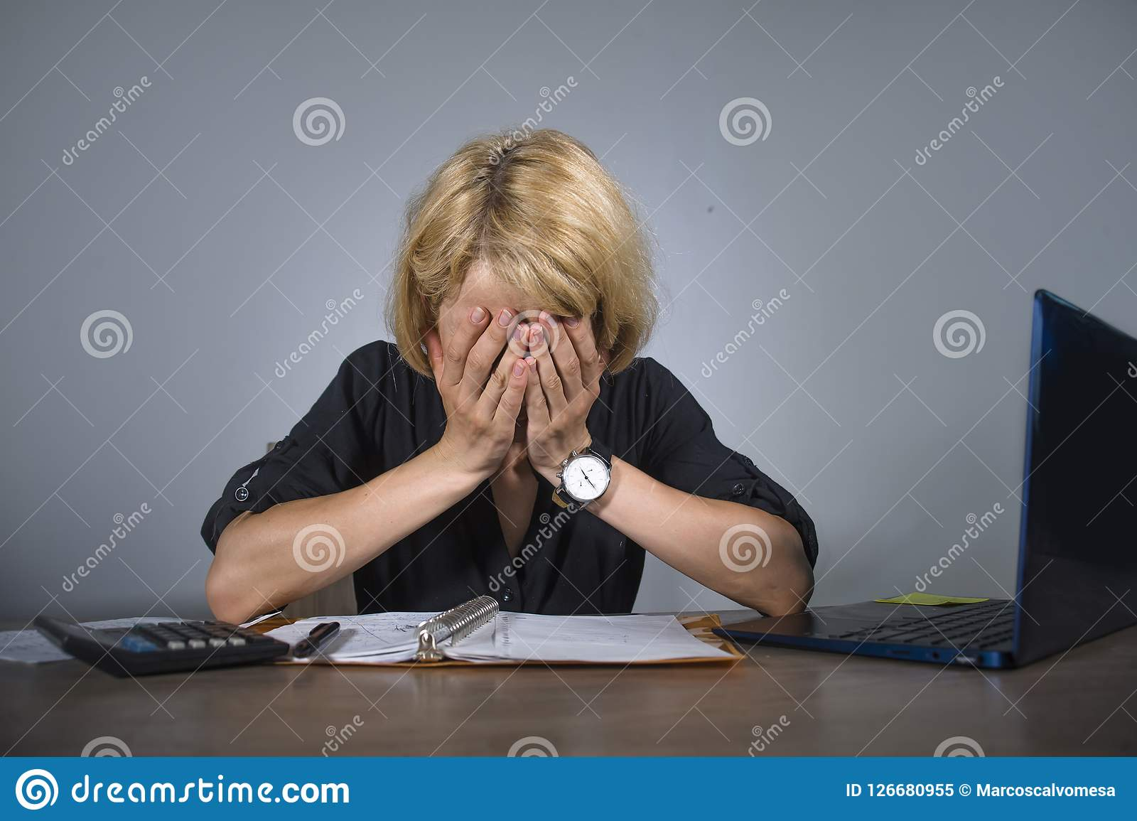 Young frustrated and stressed business woman crying sad at office desk working with laptop computer overwhelmed by paperwork workl