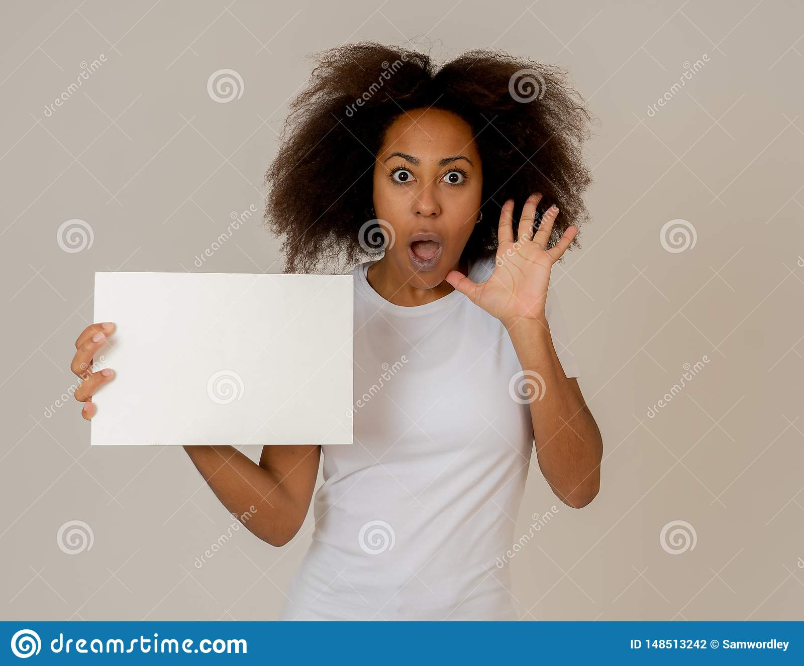 Young funny african american woman holding blank board add looking surprised and happy