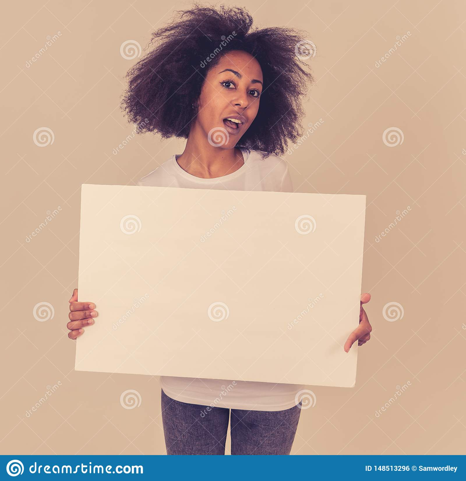 Young funny african american woman holding blank board for advertisement looking excited