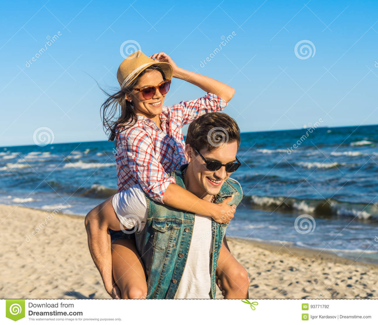 d4be8f41 Young Funny Couple In Sunglasses Piggybacking On The Beach. Stock ...