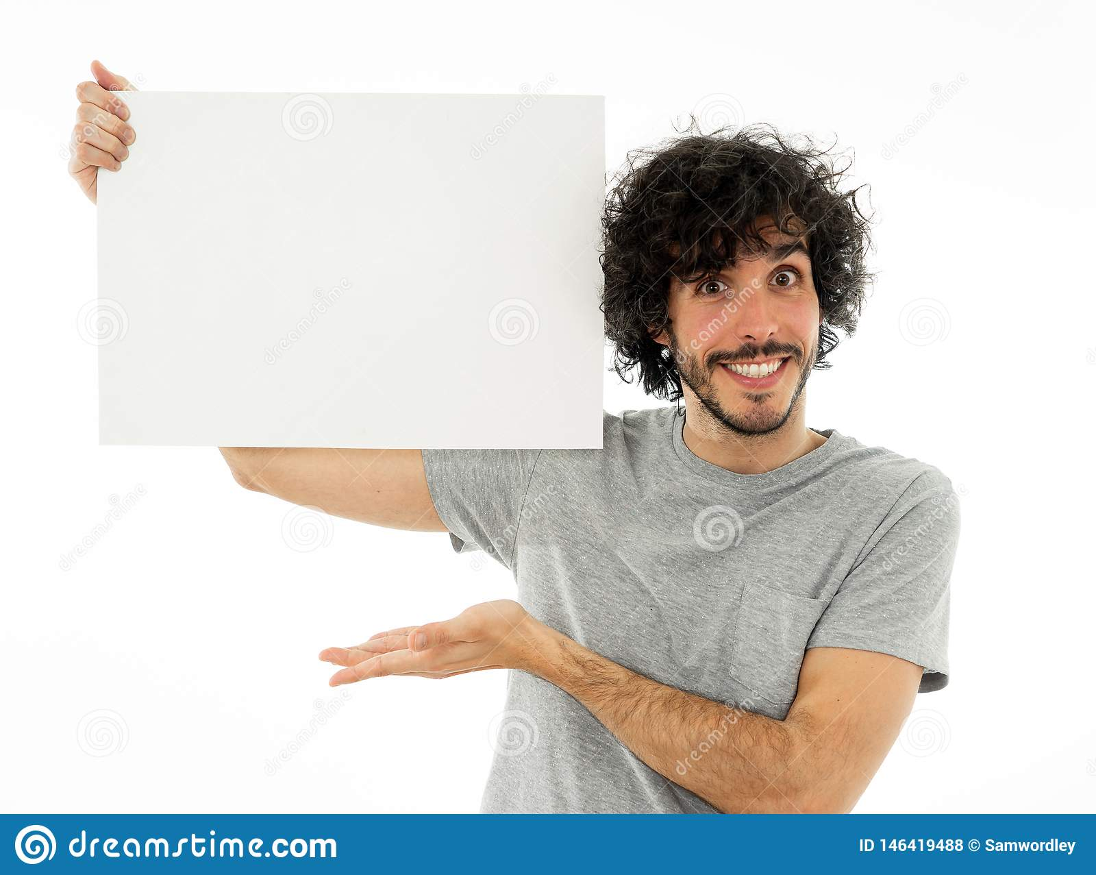 Young funny man holding blank board for advertisement. Millennial men pointing at white billboard