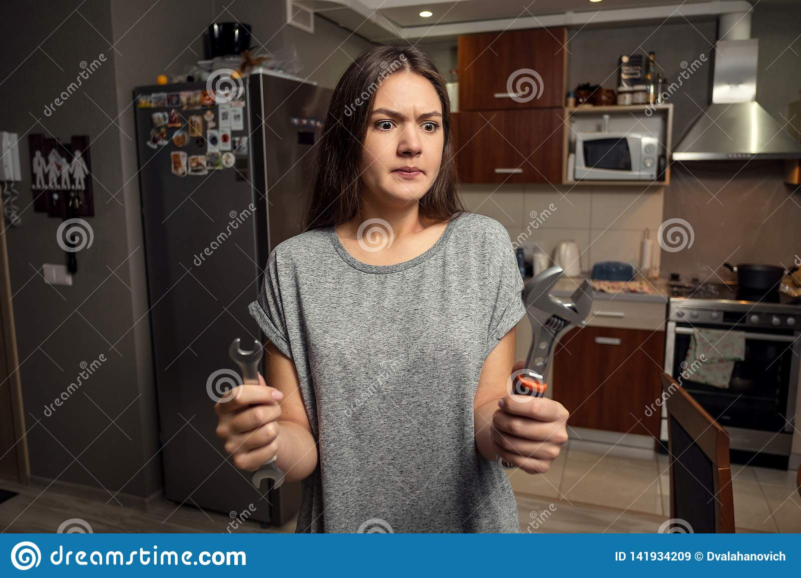Young woman holding spanners, gender equality concept