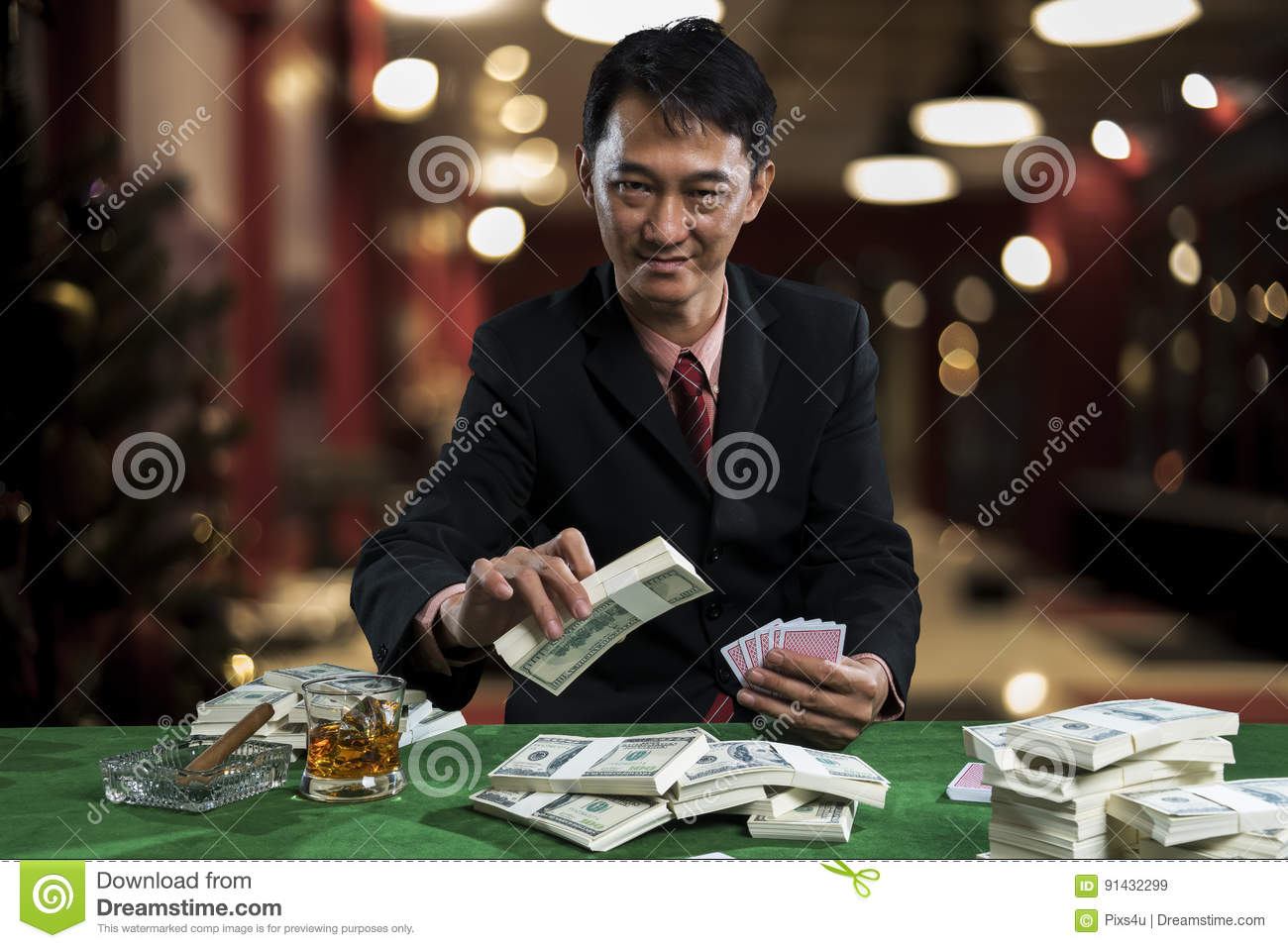 The young gambler is putting bets into the piles of banknote